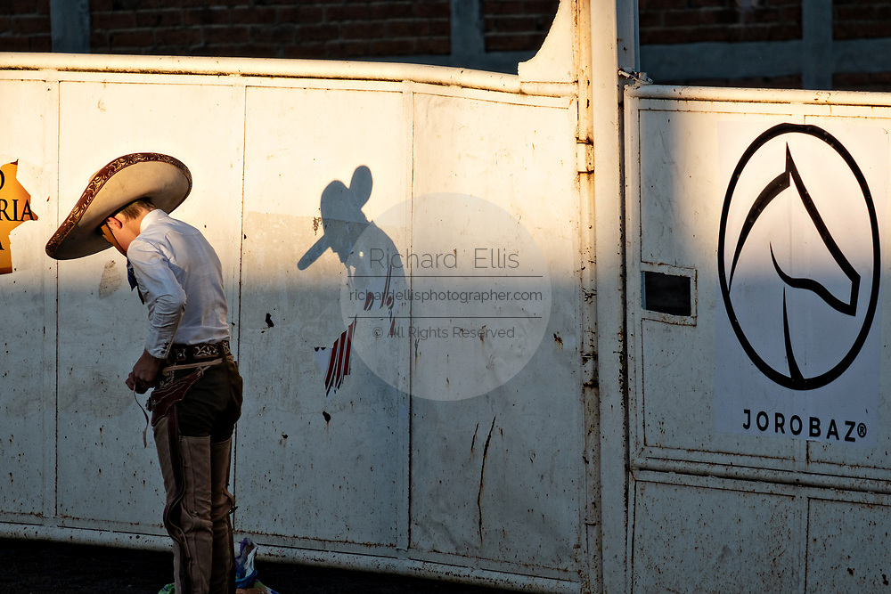 Juan Franco casts a shadow on the wall in the late afternoon during the family Charreria practice session in the Jalisco Highlands town of Capilla de Guadalupe, Mexico. The Franco family has dominated Mexican rodeo for 40-years and has won three national championships, five second places and five third places.