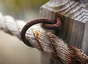 Rope is strung through rusted eyelets on the porch of an old beach cottage