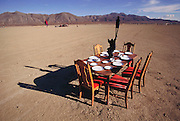 A dinner table is set in the desert at Burning Man in the late afternoon. Later that evening, 8 celebrants have dinner and then burn the table. Burning Man is a performance art festival known for art, drugs and sex. It takes place annually in the Black Rock Desert near Gerlach, Nevada, USA.
