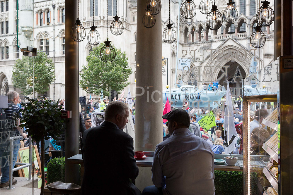 Seen through the window of a nearby cafe, environmental and climate change protesters block Fleet Street on the first day of a week-long country-wide protests using using five boats to stop traffic in Cardiff, Glasgow, Bristol, Leeds, and London, on 15th July 2019, in London, England. The group is calling on the government to declare a climate emergency, saying it was beginning a five-day summer uprising and that Ecocide ought to be a criminal offence in law.