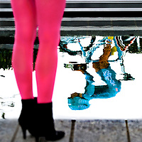 The Netherlands, Amsterdam, 08-05-2010.<br /> Cycling, Giro d'Italia, Prologue.<br /> Start of the prologue at the Museumplein. Damien Gaudin van of the Bbox Bouygues cycling team reflected in the water of the pond at the Museumplein and the pink legs of a spectator. Pink is the colour of the Giro d'Italia.<br /> Photo : Klaas Jan van der Weij