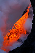 An obstruction in the path of a swift river of lava, has somewhat of an atomizing effect upon the molten fluid before it enters the sea at the Kamokuna ocean entry, on the island of Hawaii. Framed between the cliff face and the billowing steam plume, these intermittent glimpses were incredible and awe-inspiring!
