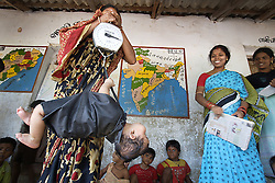 Sukanti Beua– Female, Age – 31.is the assistant to the teacher and holds the scales while weight monitoring takes place.  Here she is preparing the children to be weighed. An unnamed small child being weighed, she is not part of the pre-school.<br /> Programme: Monitoring the services of preschool centres under the Integrated Child Development Programme (ICDS).<br /> Badabhuin Pre-School Centre, Badabhuin Village, Badamba, INDIA