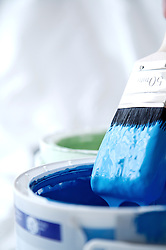 Close up of blue paint pot and dripping paintbrush