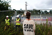 Balcombe, West Sussex. Site of Cuadrilla drilling. Demonstration against fracking 18.08.2013. Protester wearing Katherine Hammett silk t shirt , from the eighties, saying 'Save the World' and with two Nepali ex Gurkha security guards behind the fence.