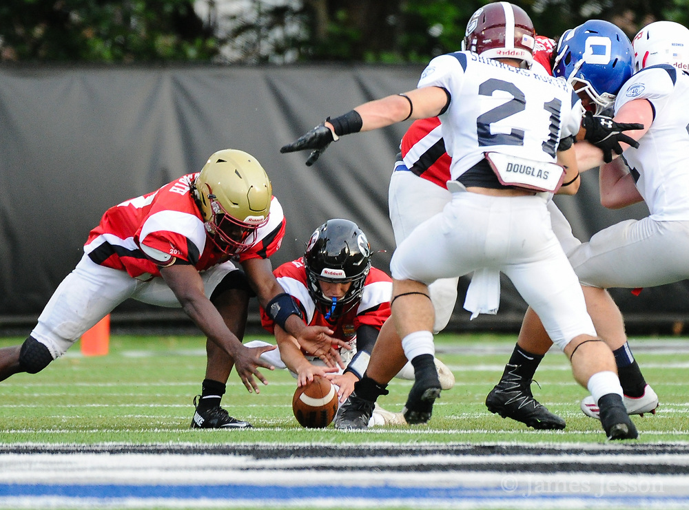 South Squad's Evan Gwozdz (center), from Middleboro High School, and Daniel Abraham (left), from Boston College High School, dive to try and recover a fumble during the Shriner's All-Star Football Classic at Bentley University in Waltham, June 22, 2018.   [Wicked Local Photo/James Jesson]
