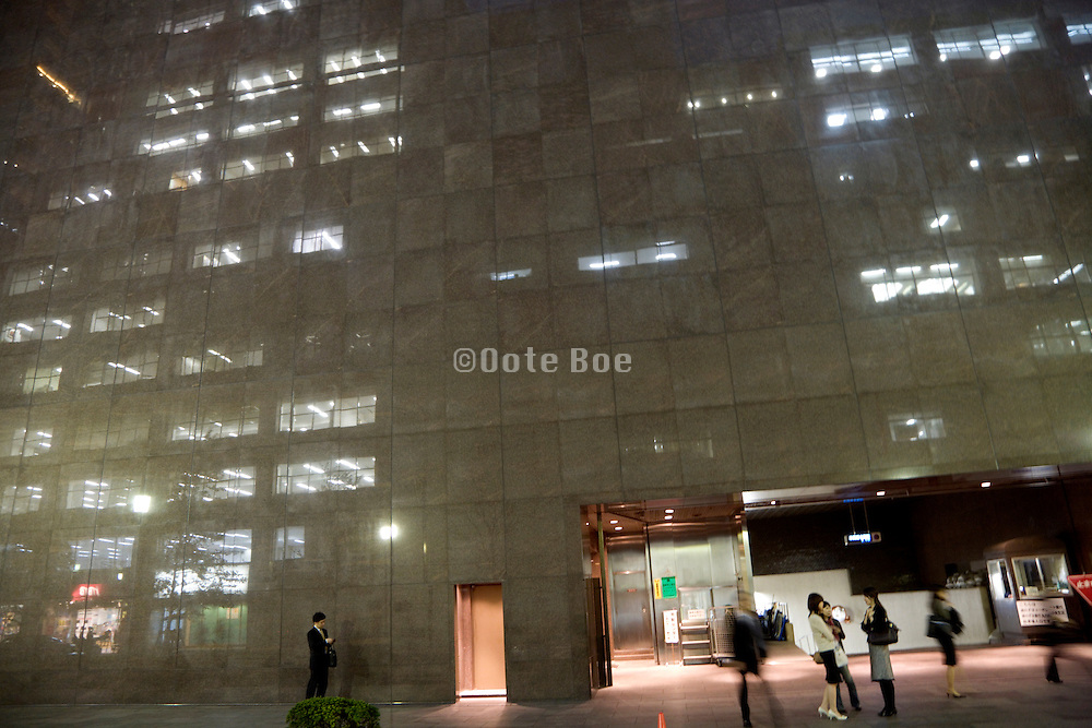 marble building with lights from offices across the street reflecting on the wall