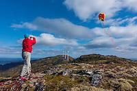 Woman flies kite on mountaintop in Kodiak, Alaska with wind turbines in background.
