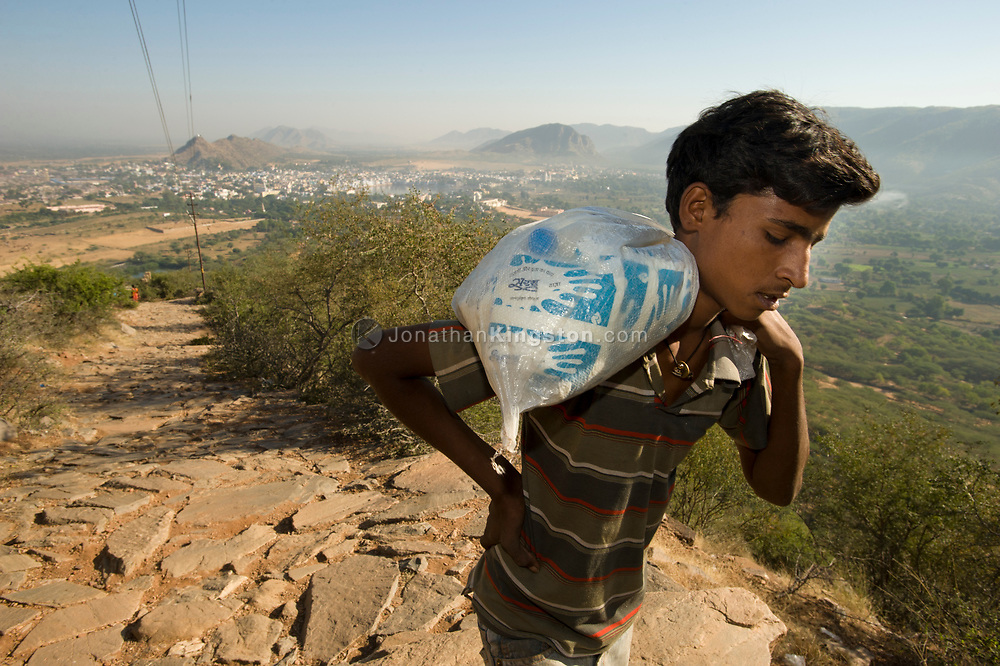 A boy carries a sack of milk to a temple in India.