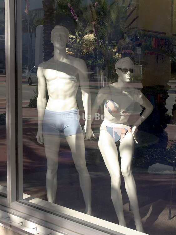 in window displayed mannequins wearing a bathing suit.