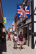 Two tourists walk beneath the sign to the John Bull, a British theme pub on 12th July 2016, at Cascais, near Lisbon, Portugal. John Bull is a national personification of the United Kingdom in general and England in particular, especially in political cartoons and similar graphic works. He is usually depicted as a stout, middle-aged, country dwelling, jolly, matter-of-fact man. Cascais is a coastal town and a municipality in Portugal, 30 kilometres 19 miles west of Lisbon. The former fishing village gained fame as a resort for Portugals royal family in the late 19th century and early 20th century. Nowadays, it is a popular vacation spot for both Portuguese and foreign tourists and located on the Estoril Coast also known as the Portuguese Riviera.