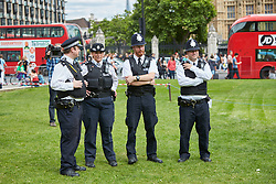 © Licensed to London News Pictures. 01/08/2015. LONDON, UK. Police watch while protesters stage a mass inhalation of nitrous oxide from balloons in Parliament Square. The so called legal high, also known as laughing gas, is set to be banned by the proposed Psychoactive Substances Bill.  Photo credit : Cliff Hide/LNP