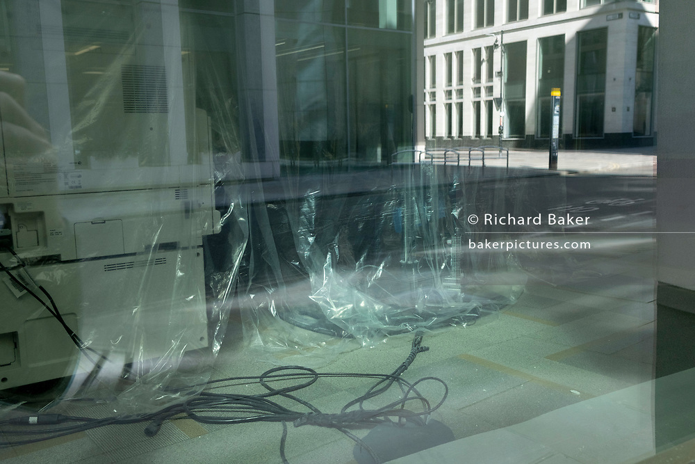 Office fixtures including computing cables and furniture are wrapped by plastic dust covers over the Easter weekend and during the third lockdown of the Coronavirus pandemic, in the City of London - the capital's financial district, on 4th April 2021, in London, England.