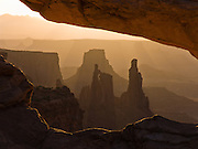 Mesa Arch frames buttes back lit by sunrise at Canyonlands National Park, Utah, USA.