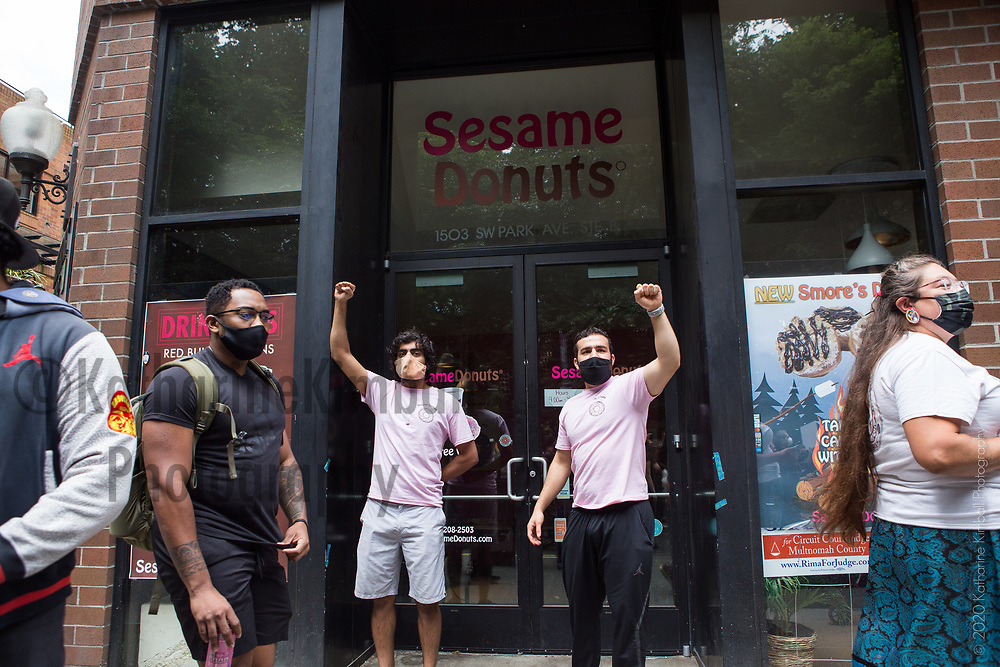 Dev Naik, left, and Yussef Fakih, raise their fists in solidarity outside Sesame Donuts as the Indigenous Solidarity March for Black Liberation passes by near Portland State University campus. Hundreds of people marched to Pioneer Courthouse Square.
