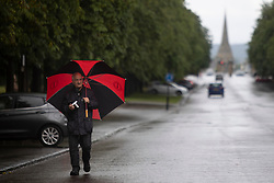 © Licensed to London News Pictures. 07/08/2021. London, UK. A man uses an umbrella to shelter from rain in Greenwich Park in South East London. A yellow weather warning for thunderstorms is in place for parts of England. Photo credit: George Cracknell Wright/LNP