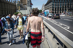 © Licensed to London News Pictures. 07/07/2017. London, UK. A man crosses Westminster Bridge holding his t-shirt as parts of the United Kingdom enjoy high temperatures and blue sky. Photo credit: Peter Macdiarmid/LNP