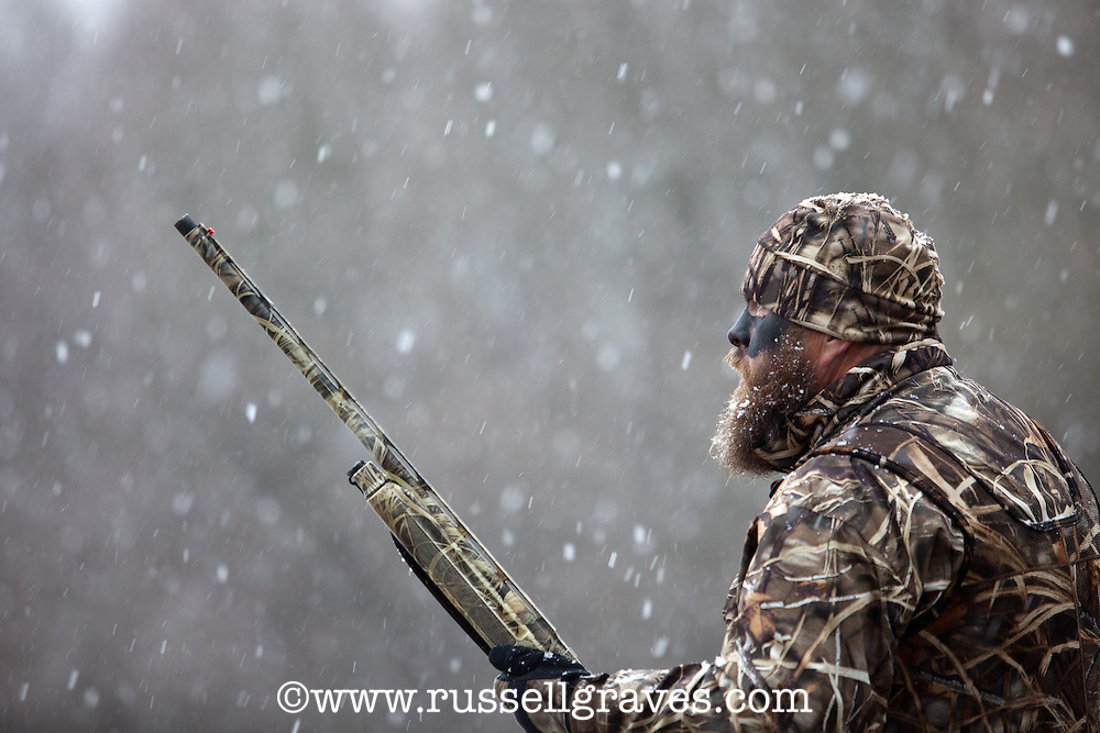 duck hunter standing in snow calling for ducks