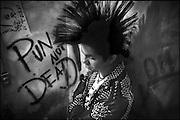 """Guadalajara, Jalisco. México 2009. El movimiento es sin duda una de las subculturas urbanas más importantes del mundo que ha conocido una fuerte expansión. Sus integrantes han desarrollado propias formas de rebeldía contra los valores del sistema dominante, expresándolo a través de transgresiones y provocaciones estéticas, musicales y culturales. Uno de los grandes temas del punk es la imposibilidad de la libertad. Sin embargo, la negación,  cuya expresión máxima es el """"anti-todo"""" es considerada, a fin de cuentas, una posibilidad de libertad. Nació como un proyecto de emancipación individual con perspectivas hacia un cambio social. Constituye una cultura de resistencia hacia toda forma de poder constituido y toda jerarquía. Los punks preconizan diferentes prácticas que manifiestan su deseo de establecer las reglas de la propia existencia: una de ellas es la filosofía del """"hazlo tú mismo"""", inspirado en la autogestión y en contra de la cultura del consumismo.  Juan tiene 20 años, es vocalista de una banda musical de rock-punk local llamada ACIDEZ, en la foto se concentra antes de un ensayo en una habitación dentro de su propia casa.<br /> Foto giorgio viera."""