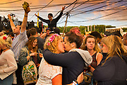 Glastonbury Festival, 2015. Shangri La is a festival of contemporary performing arts held each year within Glastonbury Festival. The theme for the 2015 Shangri La was Protest.The morning after; two owmen dancing and kissing at dawn in front of the Hell stage.