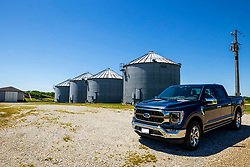 2021 Ford F150 King Ranch Super Crew in Smoked Quartz and Chrome posed in front of a set of grain storage bins in rural America