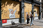 Two young women walk past a morale-boosting message written on plyboard of the boarded-up Garrick Arms pub on Charing Cross Road during the Coronavirus pandemic, on 20th August 2020, in London, England. (Richard Baker / In Pictures via Getty Images)