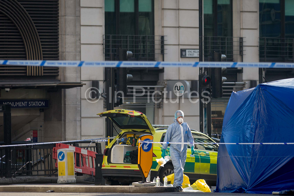 The morning after the terrorist attack at Fishmongers Hall on London Bridge, in which Usman Khan a convicted, freed terrorist killed 2 during a knife a attack, then subsequently tackled by passers-by and shot by armed police - forensic officers work on recording evidence outside one entrance to Monument Underground station, on 30th November 2019, in London, England.