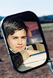 Reflection of teenage boy in side-view mirror of car