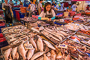 "03 OCTOBER 2012 - BANGKOK, THAILAND:    A fish vendor in her stand at Khlong Toey Market in Bangkok. Khlong Toey (also called Khlong Toei) Market is one of the largest ""wet markets"" in Thailand. Thousands of people shop in the sprawling market for fresh fruits and vegetables as well meat, fish and poultry every day.       PHOTO BY JACK KURTZ"