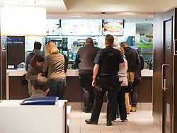© London News Pictures. 30/04/2015. A member of the Metropolitan police queueing at a McDonald's restaurant in Victoria, London to buy three drinks, while two of his colleagues wait in a police vehicle, parked on double yellow lines and using emergency lights. The police vehicle was blocking one lane of a busy road leading from Westminster through central Victoria. When the officer returned to the police vehicle the emergency lights were turned off. Photo credit: LNP