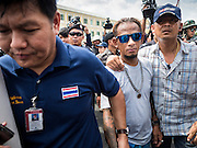 07 JULY 2015 - BANGKOK, THAILAND:  Thai police lead away a man they detained (center) during a rally in support of 14 students arrested two weeks ago. About 100 people gathered in front of the Ministry of Defense in Bangkok Tuesday to support 14 university students arrested two weeks ago for violating orders against political assembly. They're facing criminal trial in military courts. The courts ordered their release Tuesday because they can only be held for two weeks without trial, the two weeks expired Tuesday and the military court chose not to renew their pretrial detention. The court order was not an acquittal. They still face trial and possible prison sentences if convicted.       PHOTO BY JACK KURTZ