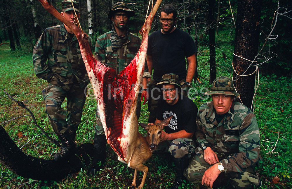 Standing with a recently-killed deer run-over on a nearby highway, members of a special US Air Force (USAF) survival course (see Corbis image 42-18212808) pose by the gutted carcass of their animal in a forest near their facility at Fairchild AFB, Spokane, Washington State. These tough-looking men host visiting air crew whose flying careers depend on passing this rigorous week of escape and evasion instruction. Should they land in enemy territory for example, they will need all the skills learned here to survive possibly weeks in the wilderness so trapping and preparing fresh meat for human consumption is of paramount importance. Here the teachers stand around the venison which is strung up on a branch, its intestines and organs already removed by a hunting knife. They wear camouflage uniforms, face paint to look vicious, threatening and heartless.