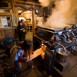 Carol Perkins loads wood into the fire under the sap evaporator at Fifield's Sugarhouse in Strafford, Vermont.