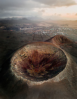 Aerial view of Calderon Hondo crater, a volcano in Timanfaya national park with a small town in background, Fuerteventura island, Canary Islands, Spain.