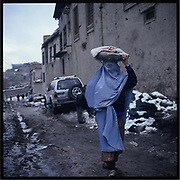 A woman carries a plate of bread in Kabul.