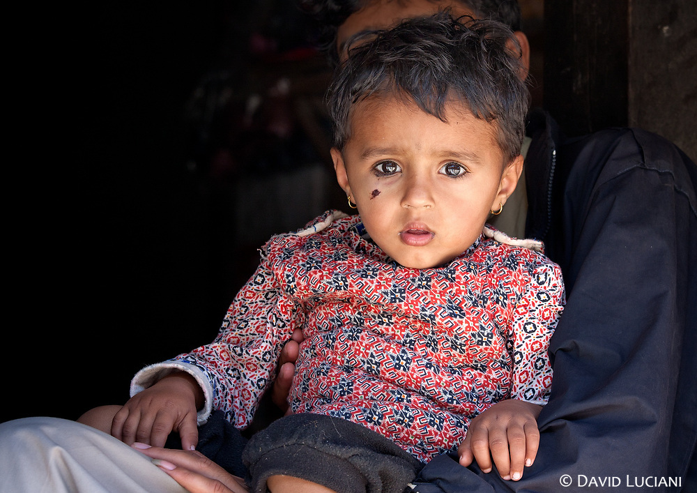 Portrait of a young girl sitting on his father's lap.