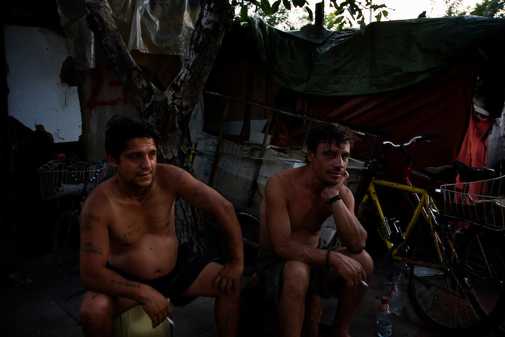 Men (Auni Morina, right) hang around in the Stara Gazela camp at dusk smoking cigarettes and drinking cheap rakija (plum brandy).