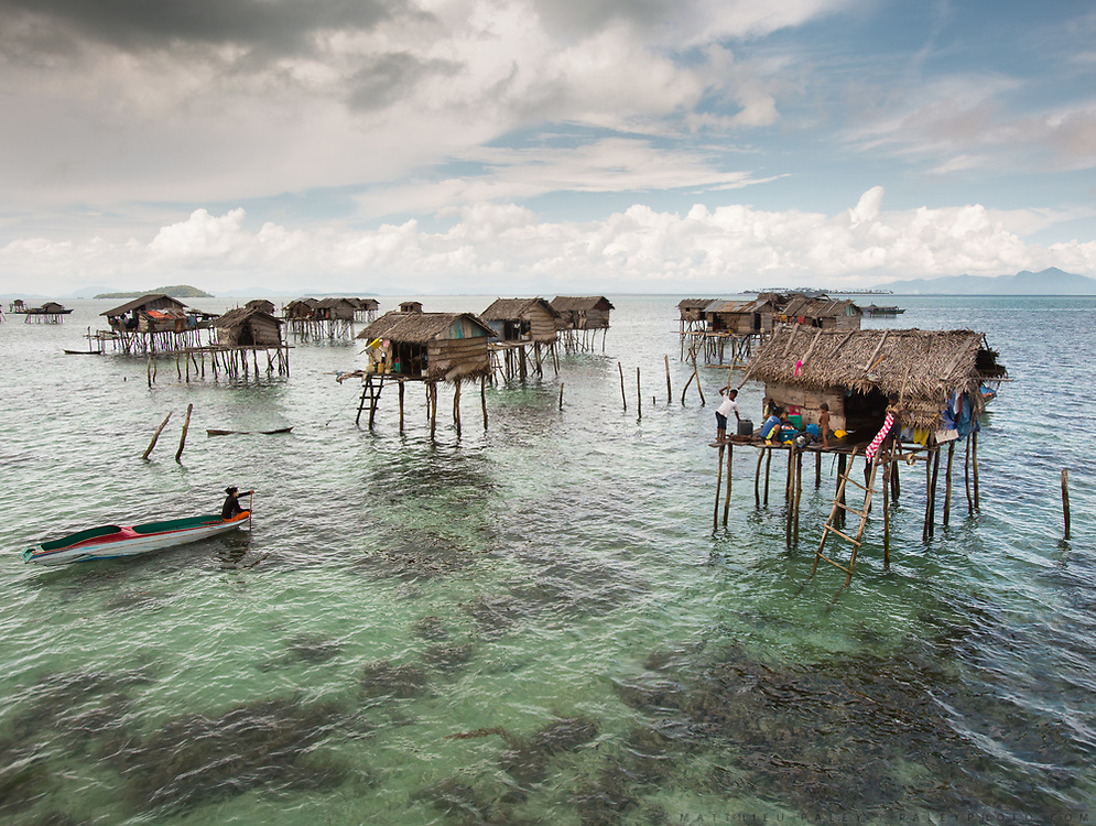 """Bajau live a seaborne lifestyle, getting their food from the ocean. They are sometimes referred to as """"Sea Gypsies"""". They often live in bamboo stilt house settlement that can only be reached by boat."""