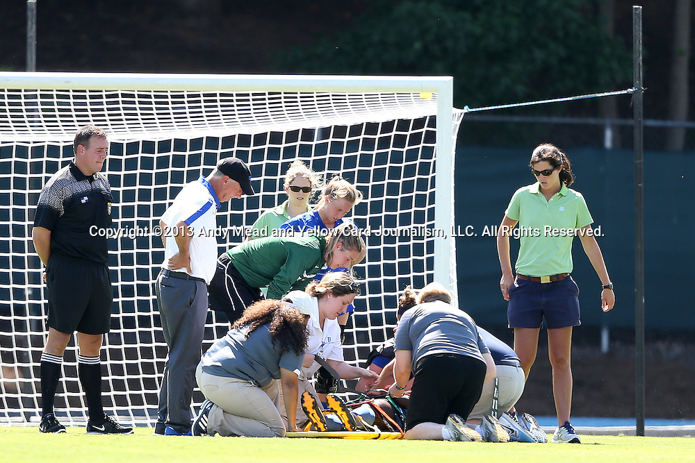 30 August 2013: Duke's Tabria Williford (in blue, on the ground) is treated by medical personal after suffering a first half injury. Teammates Meghan Thomas (dark green), Kaitlyn Kerr (blue), and head coach Robbie Church (white) check on her. The Duke University Blue Devils played the Kennesaw State University Owls at Fetzer Field in Chapel Hill, NC in a 2013 NCAA Division I Women's Soccer match. Duke won 1-0.