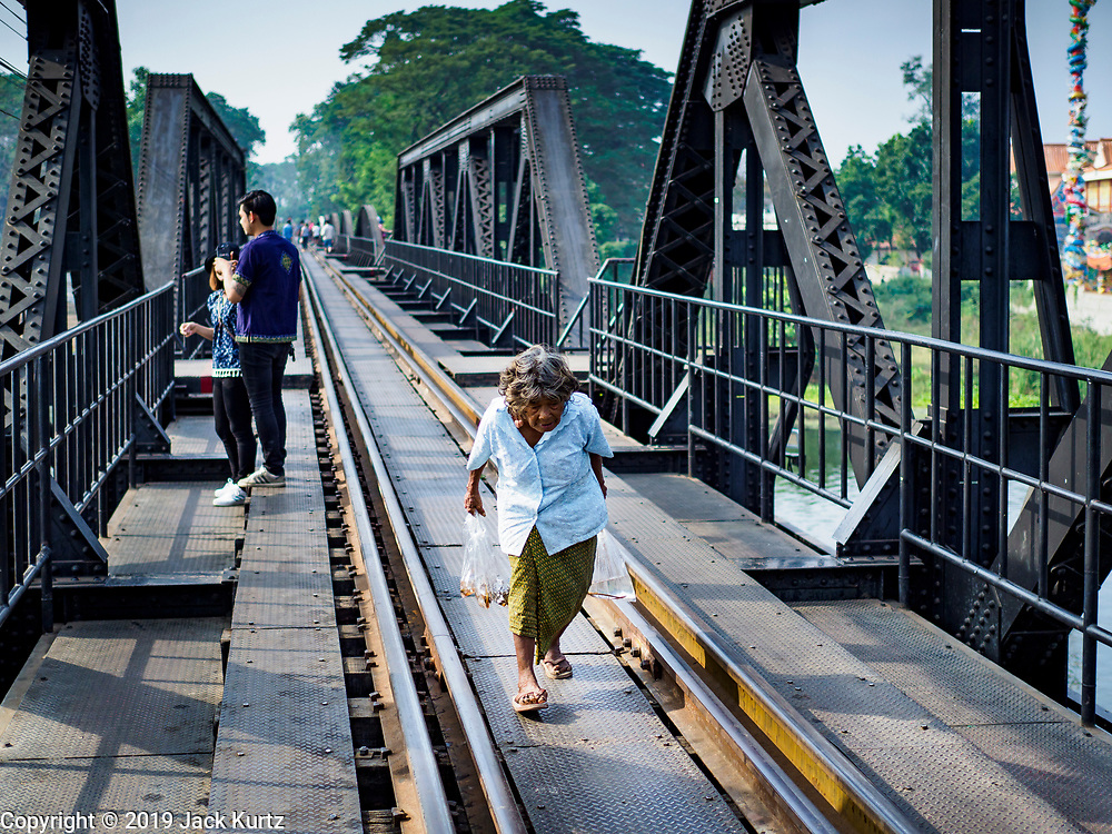 """09 JANUARY 2019 - KANCHANABURI, THAILAND: A local woman walks across the """"Bridge On the River Kwai"""" in Kanchanaburi. Hundreds of thousands of Asian slave laborers and Allied prisoners of war died in World War II constructing the """"Death Railway"""" between Bangkok and Rangoon (now Yangon), Burma (now Myanmar) for the Japanese during World War II.  The bridge is now one of the most famous tourist attractions in Thailand.     PHOTO BY JACK KURTZ"""