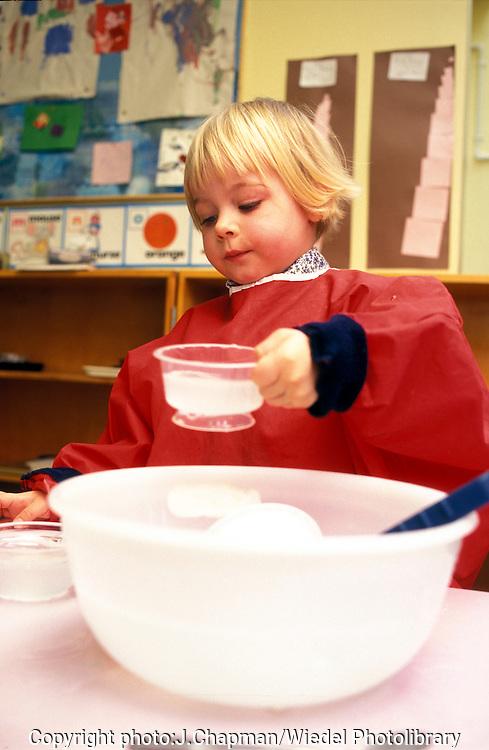 Young nursery age child measuring liquid.