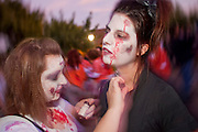 """Oct. 30, 2009 -- PHOENIX, AZ: WHITNEY KOBEY, left, helps CORY GALVAN, both Arizona State University students, put on Zombie makeup before the Zombie Walk in Phoenix Friday. About 200 people participated in the first """"Zombie Walk"""" in Phoenix, AZ, Friday night. The Zombies walked through downtown Phoenix """"attacking"""" willing victims and mixing with folks going to the theatre and downtown sports venues.  Photo by Jack Kurtz"""