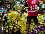 27 FEBRUARY 2019 - BANGKOK, THAILAND: A woman stacks marigold garlands in the Bangkok flower market. Bangkok, a city of about 14 million, is famous for its raucous nightlife. But Bangkok's real nightlife is seen in its markets and street stalls, many of which are open through the night.        PHOTO BY JACK KURTZ