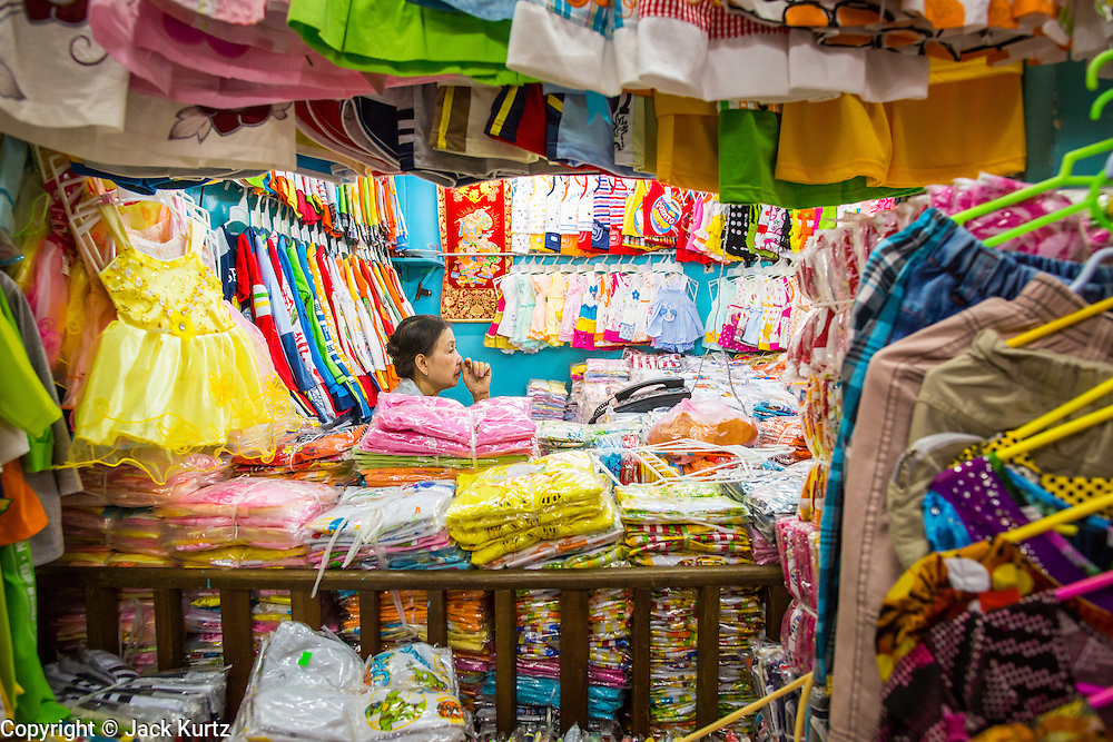 """12 APRIL 2012 - HO CHI MINH CITY, VIETNAM:   A children's clothing vendor in her shop in Binh Tay Market. Binh Tay market is the largest market in Ho Chi Minh City and is the central market of Cholon. Cholon is the Chinese-influenced section of Ho Chi Minh City (former Saigon). It is the largest """"Chinatown"""" in Vietnam. Cholon consists of the western half of District 5 as well as several adjoining neighborhoods in District 6. The Vietnamese name Cholon literally means """"big"""" (lon) """"market"""" (cho). Incorporated in 1879 as a city 11km from central Saigon. By the 1930s, it had expanded to the city limit of Saigon. On April 27, 1931, French colonial authorities merged the two cities to form Saigon-Cholon. In 1956, """"Cholon"""" was dropped from the name and the city became known as Saigon. During the Vietnam War (called the American War by the Vietnamese), soldiers and deserters from the United States Army maintained a thriving black market in Cholon, trading in various American and especially U.S Army-issue items.       PHOTO BY JACK KURTZ"""
