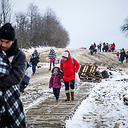 In subfreezing snowy weather, refugees walk the unoffical refugee crossing from the Tabanovce, Macedonia Train Station across the Serbian border.  A daily average of 2,200 refugees have crossed into Serbia throughout the winter.  Warmer months saw highs of 10,000 arrivals. Limited to what belongings they can carry with them, many have gone without food and water for extended periods. They have escaped their own country in conflict, taken a perilous boat ride from Turkey to Greece, and then moved onward through disorienting foreign lands in search of a peaceful home. Most refugees are headed to welcoming Germany. They are from  Afghanistan, Iraq, and Syria, with a wide range of socioeconomic backgrounds. January 2016. Produced for Mercy Corps.