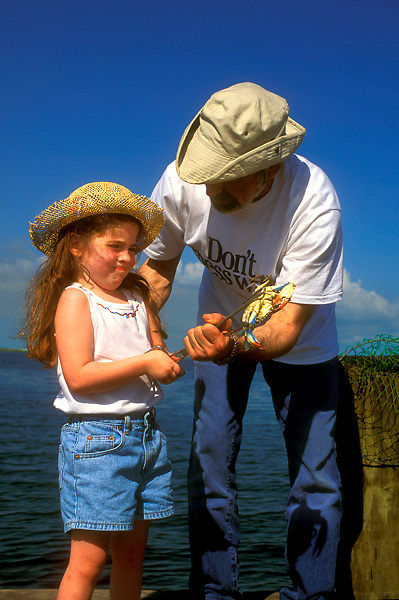 Stock photo of man with a young girl holding a blue crab on a pier