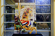 Garden City, New York, USA. March 9, 2019. After the Unveiling Ceremony of painting of closeup of Nunley's Carousel lead horse, a stallion wearing a red white and blue shoulder banner, artist Michael White's mural (approximately 7 feet high by 5 feet wide, isosceles trapezoid) is on display in carousel pavilion, on Museum Row,  Long Island.
