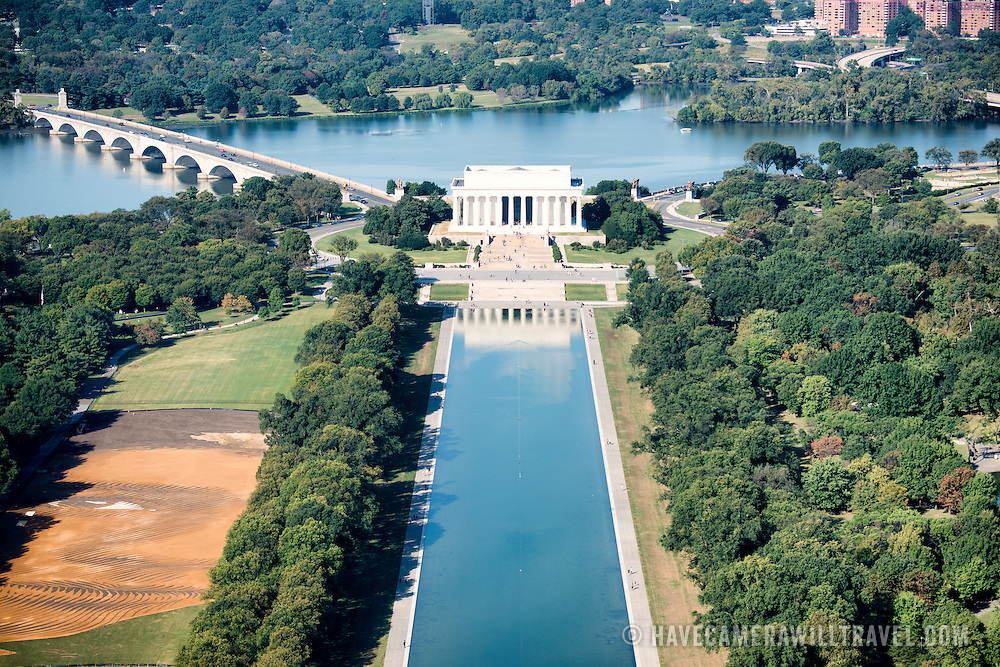An elevated view of the Lincoln Memorial and part of the Reflecting Pool as well as the Arlington Memorial Bridge as seen from the top of the Washington Monument. The Washington Monument stands at over 555 feet (169 metres) at the center of the National Mall in Washington DC. It was completed in 1884 and underwent extensive renovations in 2012-13 after an earthquake damaged some of the structure.