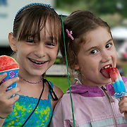 Two 8 year old girls enjoy ice cream (ices) at a festival in Wakefield, Massachusetts, USA
