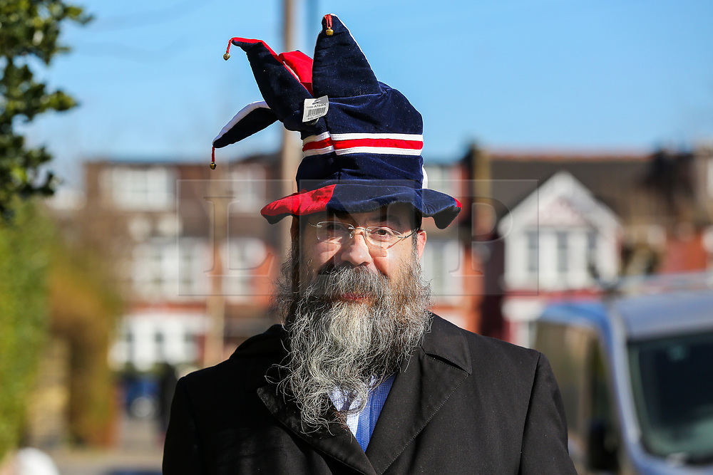 © Licensed to London News Pictures. 26/02/2021. London, UK. An orthodox Jewish man in fancy hat celebrates the festival of Purim in Stamford Hill, north London, during the Covid-19 lockdown. Purim is one of the most entertaining Jewish holidays. It commemorates the time when the Jewish people living in Persia were saved from massacre by Haman. It is customary to hold carnival-like celebrations on Purim. Stamford Hill in north London has the largest number of ultra-orthodox Charedi Hasidic Jews in Europe. Photo credit: Dinendra Haria/LNP